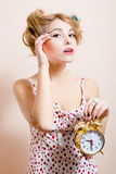 Image of attractive funny young blond pinup woman with alarm-clock looking at camera portrait Royalty Free Stock Images