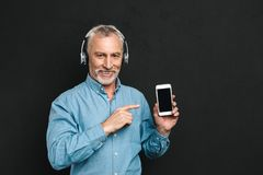 Image of attractive male pensioner 60s with gray hair pointing f. Inger on smartphone while listening to music via wireless headphones isolated over black Stock Photos