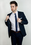 Sexy in a Suit. An image of an attractive man in a suit adjusting his jacket Stock Photos