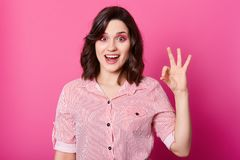 Image of attractive stylish brunette girl in striped shirt looking at camera with opened mouth and showing ok gesture, stock photos