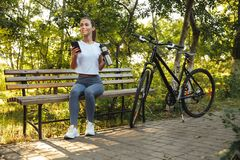 Image of attractive woman sitting on bench in park with bicycle, and using cell phone stock photo