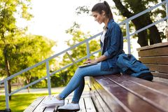 Young beautiful woman sitting outdoors using laptop computer. royalty free stock images