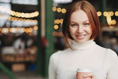 Image of attractive young woman with brown hair, gentle smile, wears white turtleneck sweater, holds paper cup of coffee, has stock image