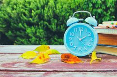 Image of autumn Time Change. Fall back concept. Dry leaves and vintage alarm Clock stock images
