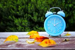 Image of autumn Time Change. Fall back concept. Dry leaves and vintage alarm Clock on wooden table outdoors at afternoon stock photography