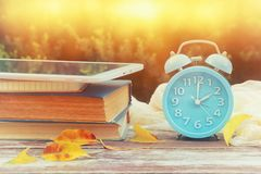 Image of autumn Time Change. Fall back concept. Dry leaves and vintage alarm Clock on wooden table outdoors at afternoon.  stock photos