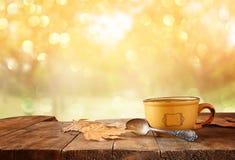 Image avant de tasse de café au-dessus de table et de feuilles d'automne en bois devant le fond automnal de coucher du soleil Photo stock