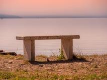 Image avec le banc en pierre devant un lac avec la vue de coucher du soleil photo libre de droits