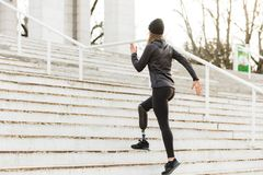 Image from back of energetic disabled girl with prosthetic leg i. N sportswear working out and running at the stairs in stadium royalty free stock images