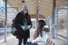 Image of Backpacker woman talking whit her friend on train station platfo royalty free stock photos