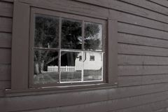 Image of backyard relected in old paned window. Set in weatherboard wall stock photography