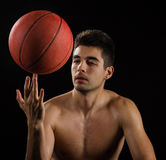 Image of a basketball player spinning a ball on finger. Basketball player spinning a basketball on finger, on black background Stock Photography