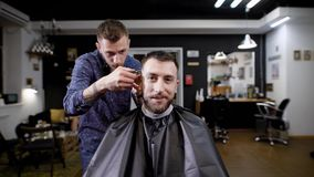 Image of bearded hipster sitting in the barbershop covered with black peignoir. Barber dressed in casual clothes stock footage