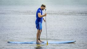 A bearded man paddling in the ocean. An image of a bearded man paddling in the ocean stock photos