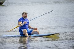 A bearded man paddling in the ocean. An image of a bearded man paddling in the ocean stock photography