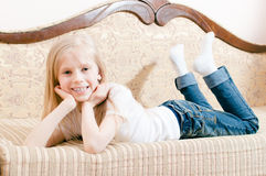 Image of beautiful blond child girl with blue eyes lying on stomach propped head with her hands happy smiling Stock Image