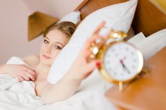 Image of beautiful blond young business woman blue eyes girl touching alarm clock off wake up time looking at camera happy smiling Stock Photos