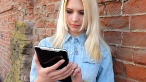 Image of beautiful blond young lady using tablet stock footage