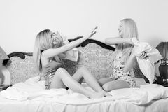 Image of beautiful blond young women, cute 2 sisters or sexy girl friends in pajamas having fun fighting pillows on the. Black and white image of beautiful blond Stock Image