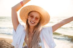 Image of beautiful blonde woman 20s in summer straw hat and sung. Lasses smiling while resting at seaside Royalty Free Stock Photos