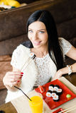 Image of beautiful brunette young woman eating tasty sushi having fun happy smiling sitting in restaurant & looking at camera Stock Photos