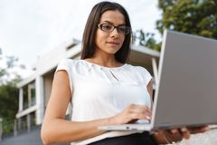 Beautiful business woman posing outdoors at the street using laptop computer. Image of a beautiful business woman posing outdoors at the street using laptop royalty free stock image