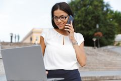 Beautiful business woman posing outdoors at the street using laptop computer talking by phone. Image of a beautiful business woman posing outdoors at the street royalty free stock images