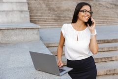 Beautiful business woman posing outdoors at the street using laptop computer talking by phone. Image of a beautiful business woman posing outdoors at the street stock photography