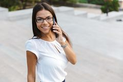 Beautiful business woman walking outdoors talking by mobile phone. Image of a beautiful business woman walking outdoors talking by mobile phone royalty free stock photo