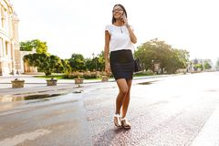 Beautiful business woman walking outdoors talking by mobile phone royalty free stock photos