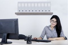 Beautiful businesswoman smiling at the camera. Image of beautiful businesswoman smiling at the camera while working with a computer in the office Stock Photo