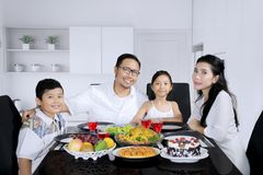 Beautiful family having a dinner together. Image of beautiful family looking at the camera while having a dinner together in the kitchen royalty free stock photography
