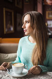 The image of a beautiful girl in a cafe. Pretty caucasian woman having coffee at the restaurant Royalty Free Stock Images