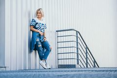 Image beautiful girl with short white hair. Dressed in jeans in urban style. Place for text stock image