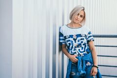 Image beautiful girl with short white hair. Dressed in jeans in urban style. Place for text royalty free stock photo