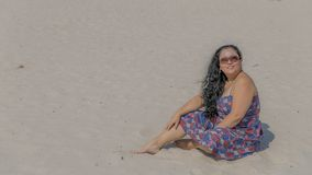 Image of a beautiful happy and smiling woman sitting on the sand in a blue dress with red and white flowers. And sunglasses enjoying a wonderful sunny day in stock image