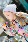 Image of beautiful little blond girl having fun playing blowing soap bubbles on the spring or autumn outdoors background Royalty Free Stock Photos