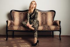 The image of a beautiful luxurious woman sitting on a gold vintage couch.  Stock Photo