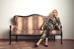 The image of a beautiful luxurious woman sitting on a vintage couch.  Stock Photography
