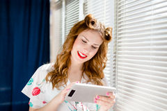 Image of beautiful pinup girl reading on tablet pc and smiling at home by sun lighted window blinds. Young pretty woman holding tablet pc computer and smiling Stock Photos