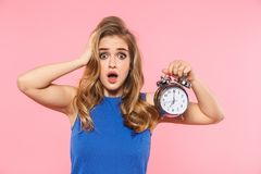 Shocked displeased young pretty woman posing isolated over pink wall background holding alarm clock stock image
