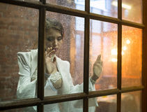 Image of the beautiful woman behind the glass Stock Images