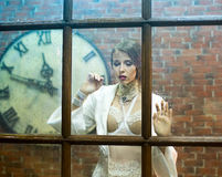 Image of the beautiful woman behind the glass Stock Photography