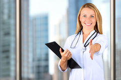 Image of beautiful woman doctor looking at camera and giving a hand royalty free stock photo