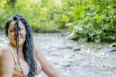 Image of a beautiful woman with long black hair on her face enjoying a wonderful and sunny summer. Day with the river Ahr in Schuld, Germany with green stock images