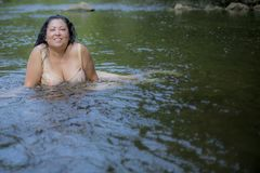 Image of a beautiful woman with long black hair swimming in the river. Ahr on a wonderful summer day in Schuld, Germany royalty free stock photos