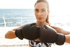 Beautiful young sports fitness woman boxer make exercises in gloves at the beach outdoors royalty free stock photo