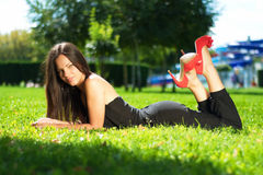 Image of a beautiful young woman lying and posing in green grass Royalty Free Stock Image