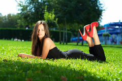 Image of a beautiful young woman lying and posing in green grass Stock Image