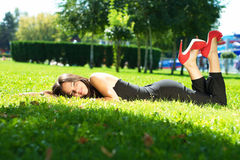 Image of a beautiful young woman lying and posing in green grass Stock Images